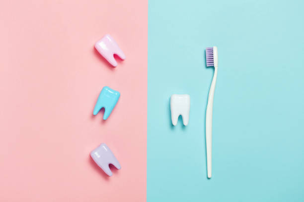 Big teeth on blue and pink background. Minimal Toothbrush and big tooth on blue and pink background. Teeth care minimalism concept. toothbrush stock pictures, royalty-free photos & images