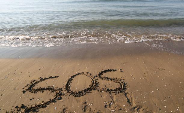 großer text sos auf dem sand des strandes - sos einzelwort stock-fotos und bilder