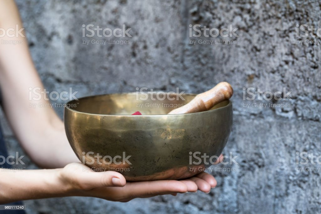 Big Tibetan singing bowl in the hands of a woman stock photo