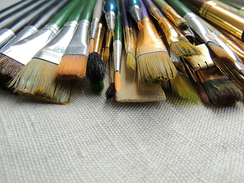 Big variety of brushes, tools for painting and sculpture on linen fabric background.