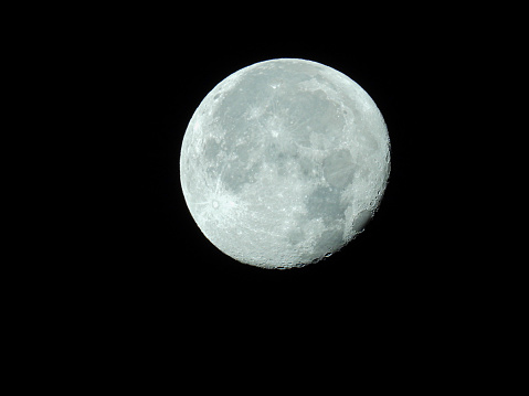 big waning moon with its moon craters in the black night sky