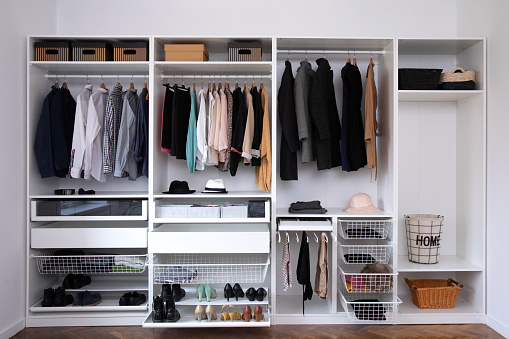 Stylish clothes, shoes and home stuff in large wardrobe closet. Dressing room interior with big wardrobe