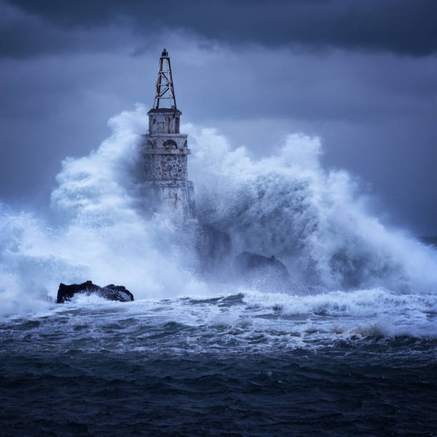 Big wave against old Lighthouse in the port of Ahtopol, Black Sea, Bulgaria on a moody stormy day. Danger, dramatic scene. stock photo
