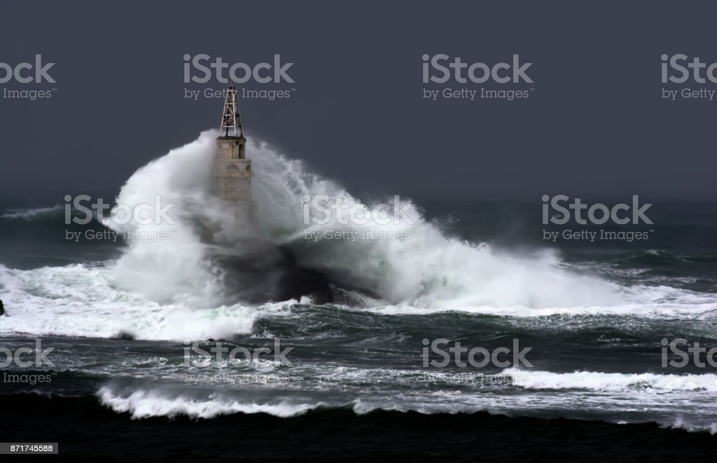 Big wave against  old Lighthouse in the port of Ahtopol, Black Sea, Bulgaria on a stormy day. stock photo