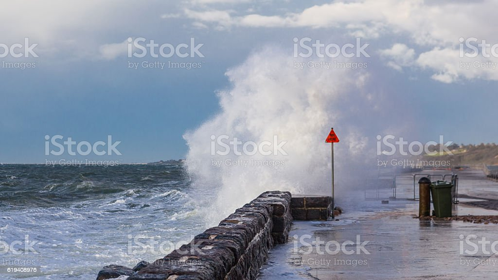 Big wave breaking over pier stock photo