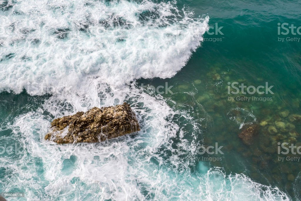 Big waves breaking on the shore. Waves and white foam. Coastal stones. View from above. The marine background is green royalty-free stock photo