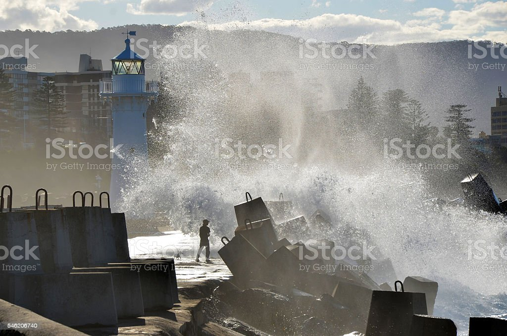 Big waves breaking over a man and dog stock photo