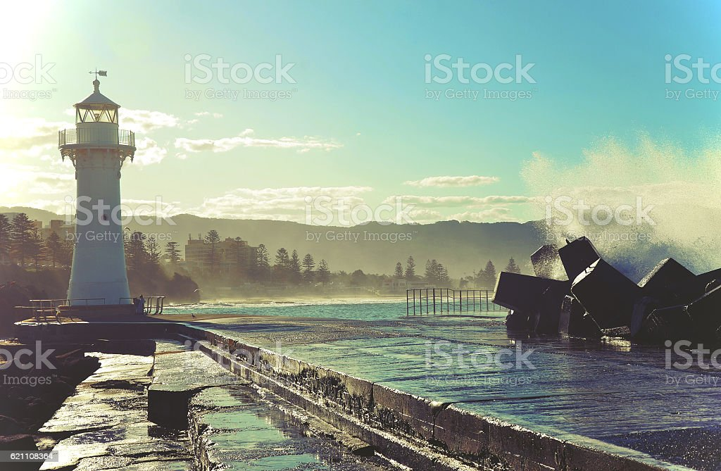 Big waves breaking over Wollongong harbor breakwall and lighthouse stock photo
