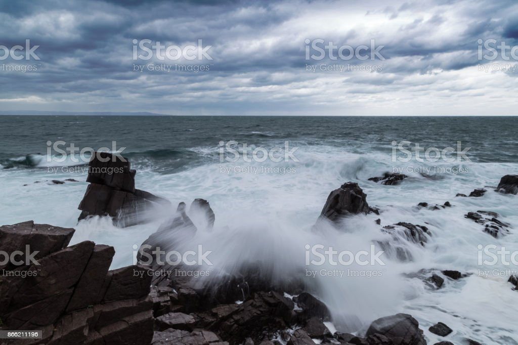 Big waves crash in the cliff on the rocky beach stock photo