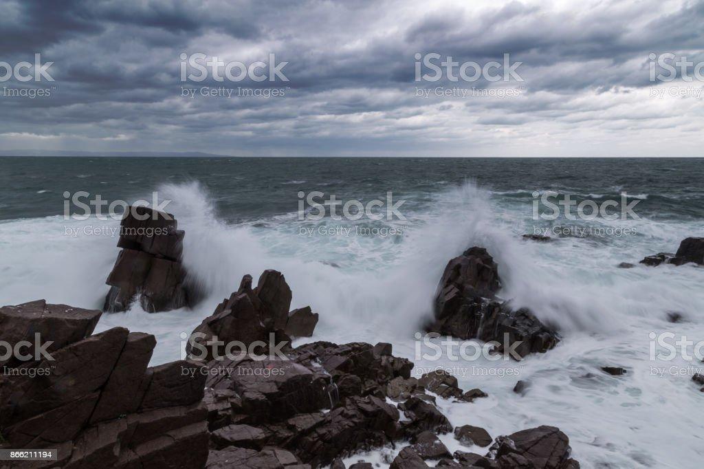 Big waves crash on the rocky beach stock photo