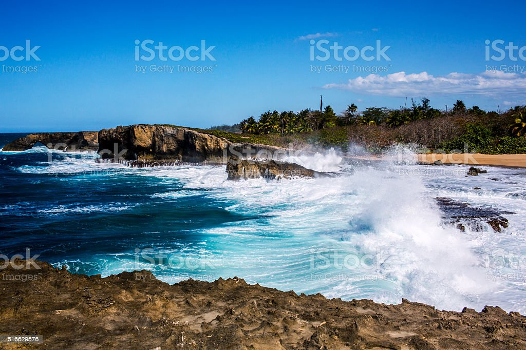 Big waves crashing on rocky shore stock photo