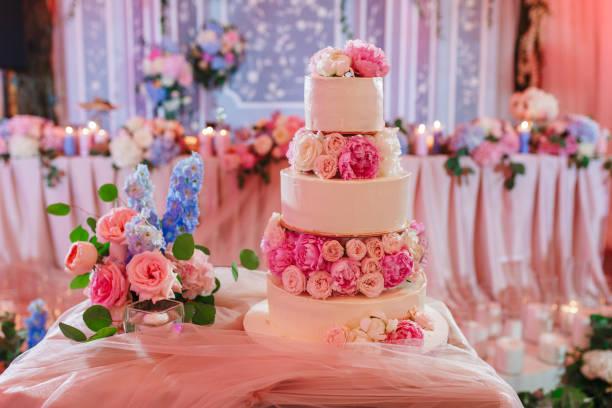 Gros gâteau de mariage sur la table de réception décorée de roses pivoine - Photo