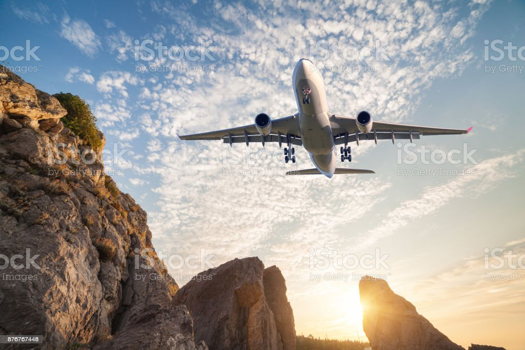 Big white aircraft is flying over rocks at sunset. Landscape with passenger airplane, mountains, colorful blue sky with clouds. Passenger airplane is landing. Business travel. Commercial plane. stock photo