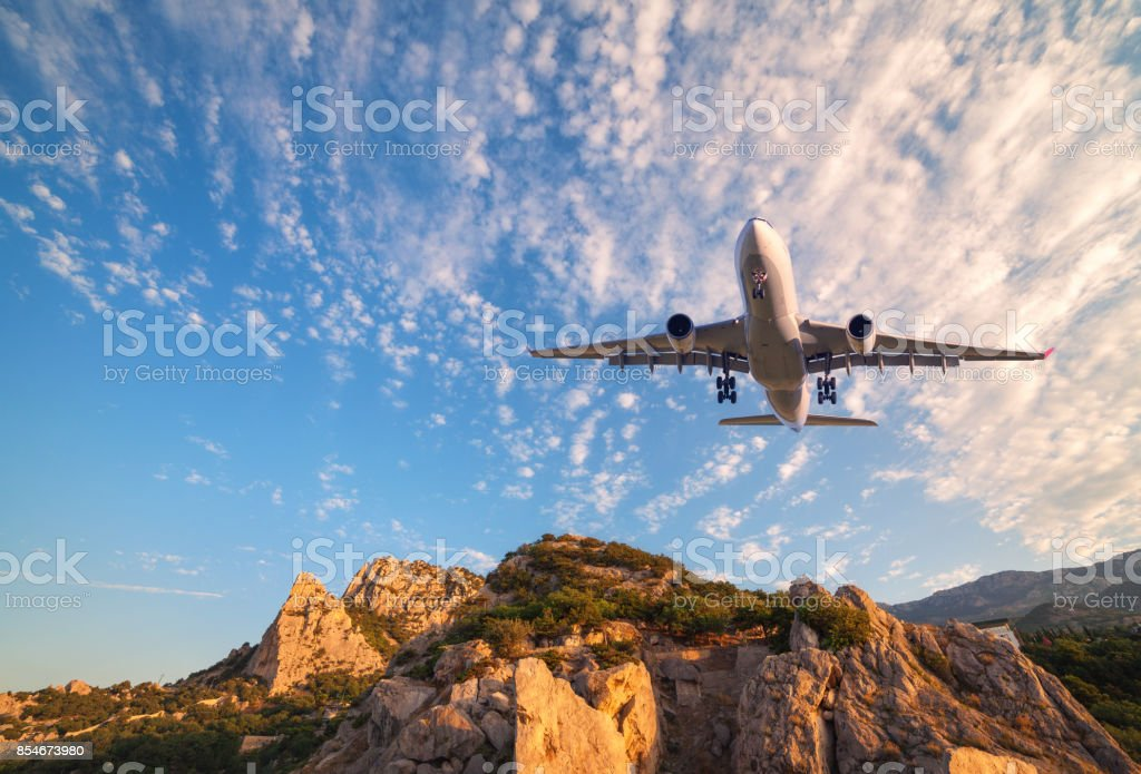 Big white airplane is flying over rocks at sunrise. Landscape with passenger airplane, mountains, colorful blue sky with clouds. Passenger aircraft is landing. Business travel. Commercial plane. stock photo