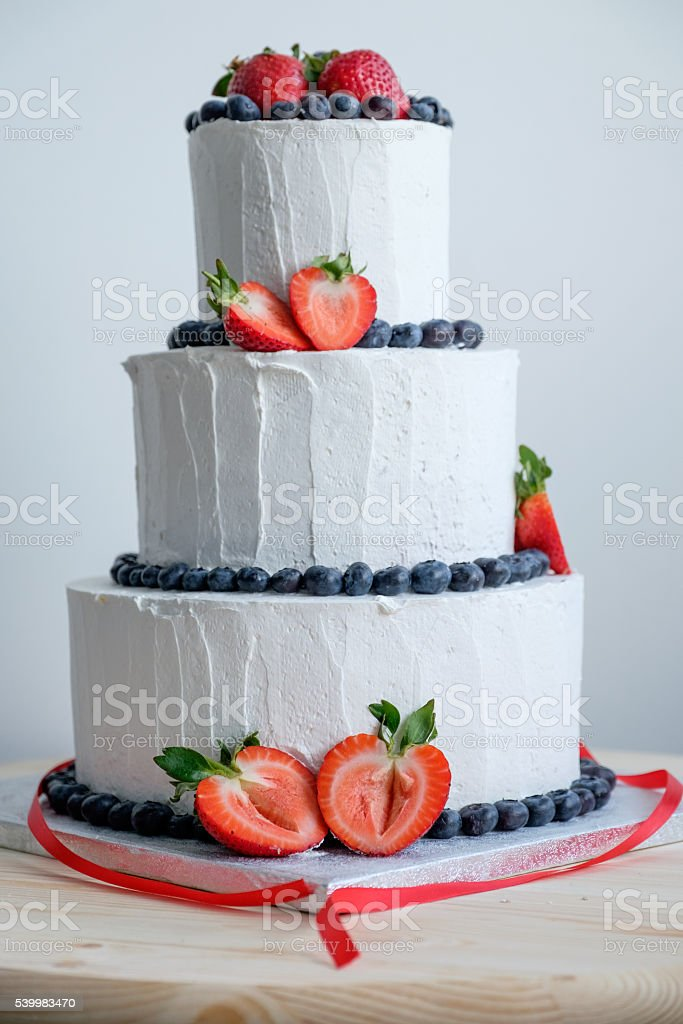 big white cake decorated with red strawberry and black berry stock photo