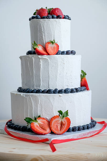 big white cake decorated with red strawberry and black berry - big cake stock photos and pictures