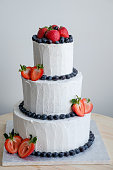 side view on big white cake decorated with red strawberry and black berry