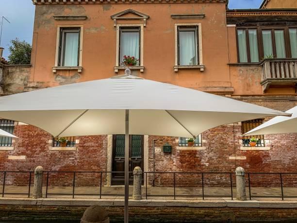 grand parasol blanc sur mur de brique - josianne toubeix photos et images de collection