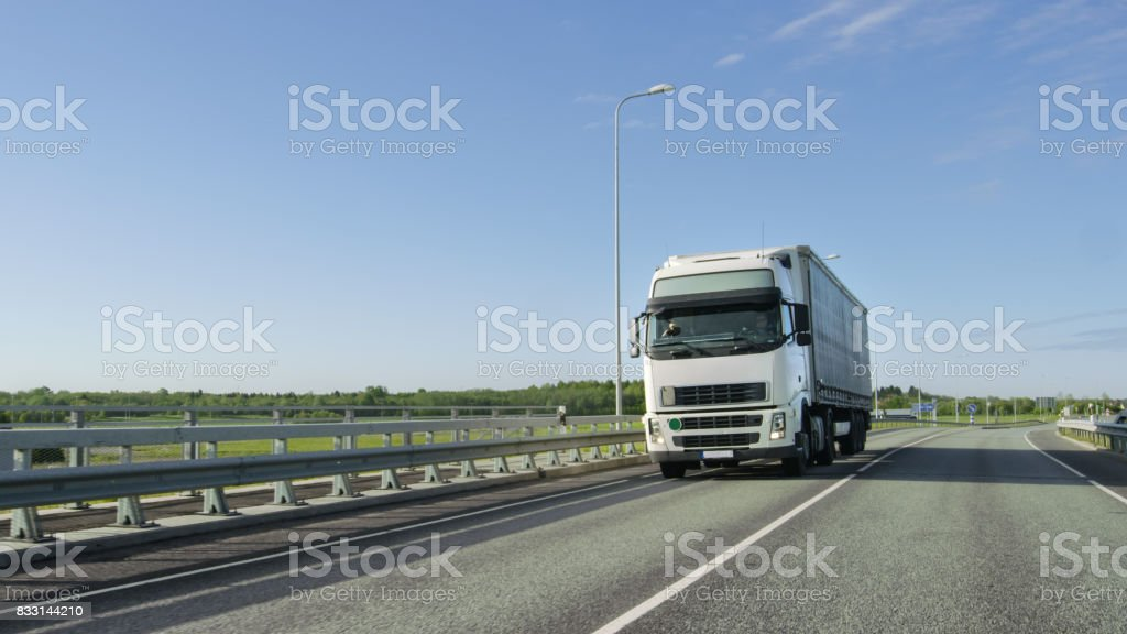 Big White Semi Truck with Cargo Trailer Drives on the Industrial Area Empty Road With Sun Shining in the Background. stock photo