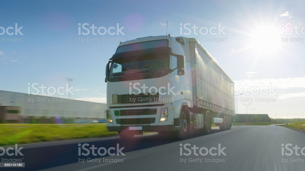 Big White Semi Truck with Cargo Trailer Moves on the Industrial Area Empty Road With Sun Shining in the Background. Blur motion. stock photo