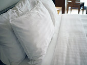 Big white soft pillows on a white luxury cozy bed with clean white sheets. Healthy sleep, deep relaxing and comfortable concept. Selective focus.