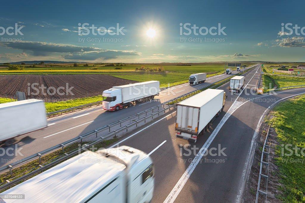 Blanco grande camiones en la autopista en la idílica soleada a la mañana - foto de stock