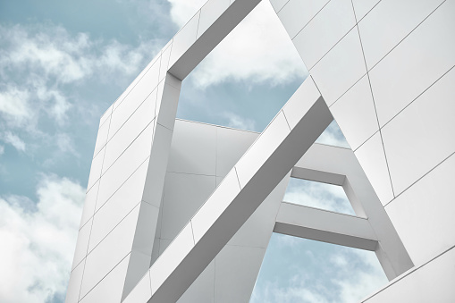 Big white walls of the building against the blue sky and white clouds. Modern architecture. Minimalistic design