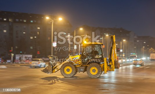 istock Big yellow loader bulldozer earth mover or digger construction machinery on the street with motion blur from driving night image with film grain 1130303238