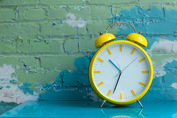 Big yellow retro style alarm clock stock photo