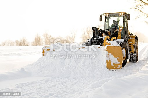 A yellow snow plow cleaning a road