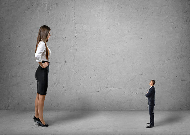 big young businesswoman standing in front of small businessman - man dominating woman stock photos and pictures