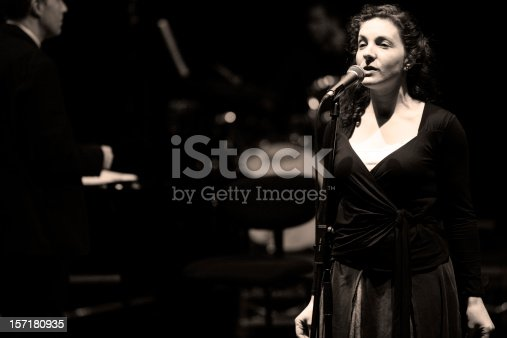 Solo female vocalist on stage with elements of a big band visible in the background.