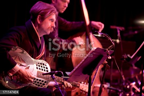 A pair of session musicians take notice of the conductor during a performance.