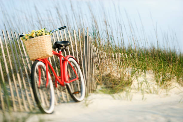 Bike by fence at beach. stock photo