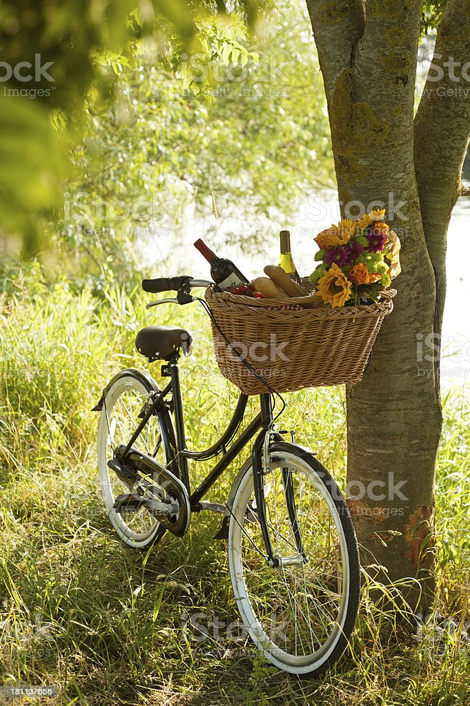 Bike by the river with picnic supplies in basket stock photo