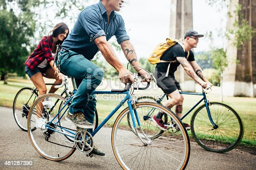 A mixed-race group of friends commuting in an urban city environment with trees in background. This happy trio is excited for their fun adventure.  Horizontal with copy space.  Three people riding their bicycles.