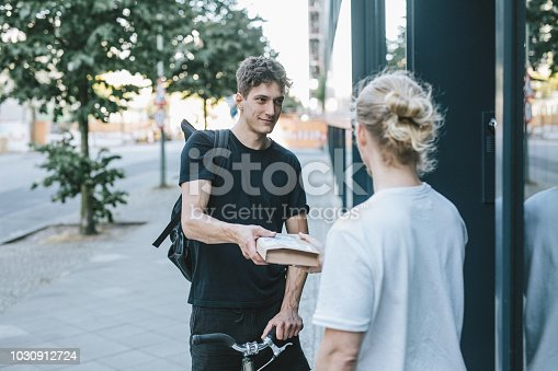 Candid picture of a young bike messenger delivering a box to a man