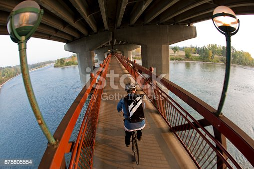 A male bike messenger rides over a river on a bridge on his way to make a delivery. He is riding a fixed gear or one speed bicycle.