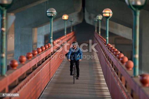 A male bike messenger rides over a bridge on his way to make a delivery. He is riding a fixed gear or one speed bicycle.