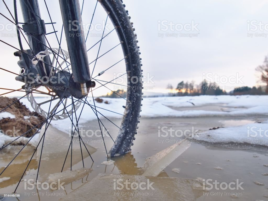 Bike drowned in muddy pool within winter trip. Broken pieces of ice around freeze terain tyre stock photo