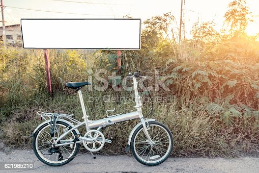istock Bike folding parked on meadow with white poster 621985210