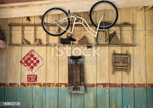 Classic old bike hanging in weathered garage with various objects neatly hanging alongside
