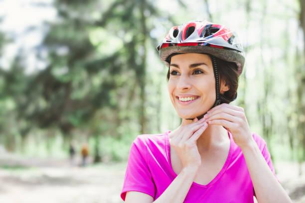 bike helmet. woman putting biking helmet on outside during bicycle ride. - kask sportowy zdjęcia i obrazy z banku zdjęć