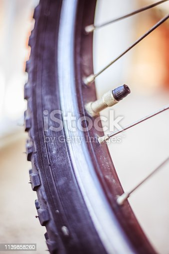 Close up picture of a bike tyre outlet and spokes, blurry background