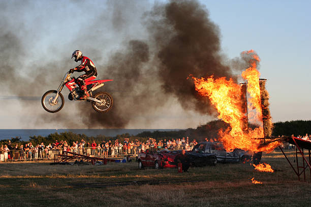 bike jumping through fire - daredevil stock pictures, royalty-free photos & images