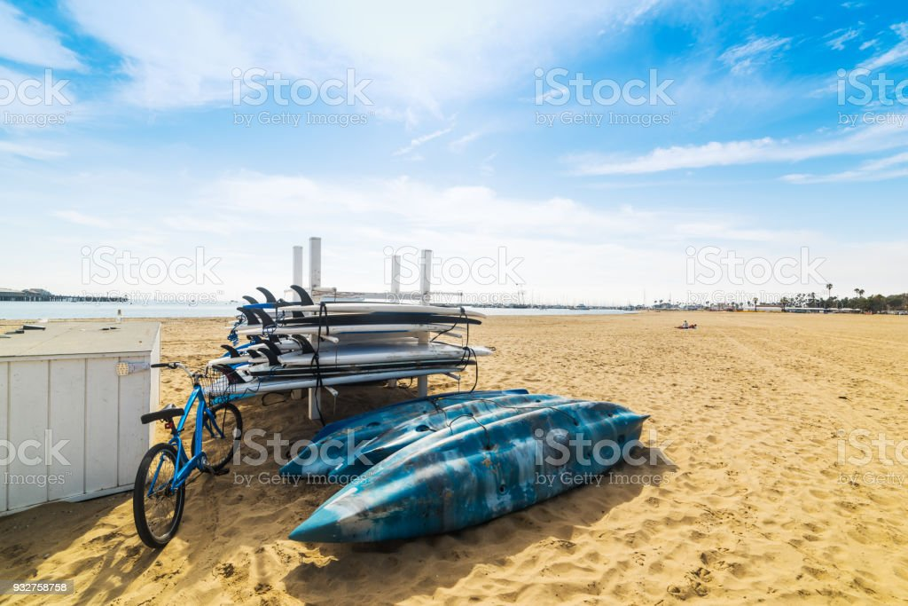 Bike, kayaks and surfboards on the sand stock photo