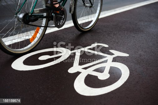 Bike lane on a rainy day. Sign for bicycle painted on the asphalt. Dividing line, diminishing perspective.