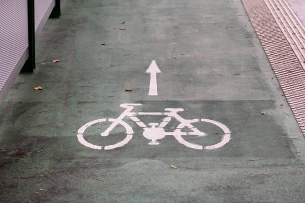 Símbolo da pista da bicicleta com uma seta do sentido na terra. Sinal de estrada da fuga da bicicleta na ponte moderna para a bicicleta e os ciclistas na cidade urbana. Viagens, turismo, transporte, tráfego. Sinal da bicicleta na superfície da rua. - foto de acervo