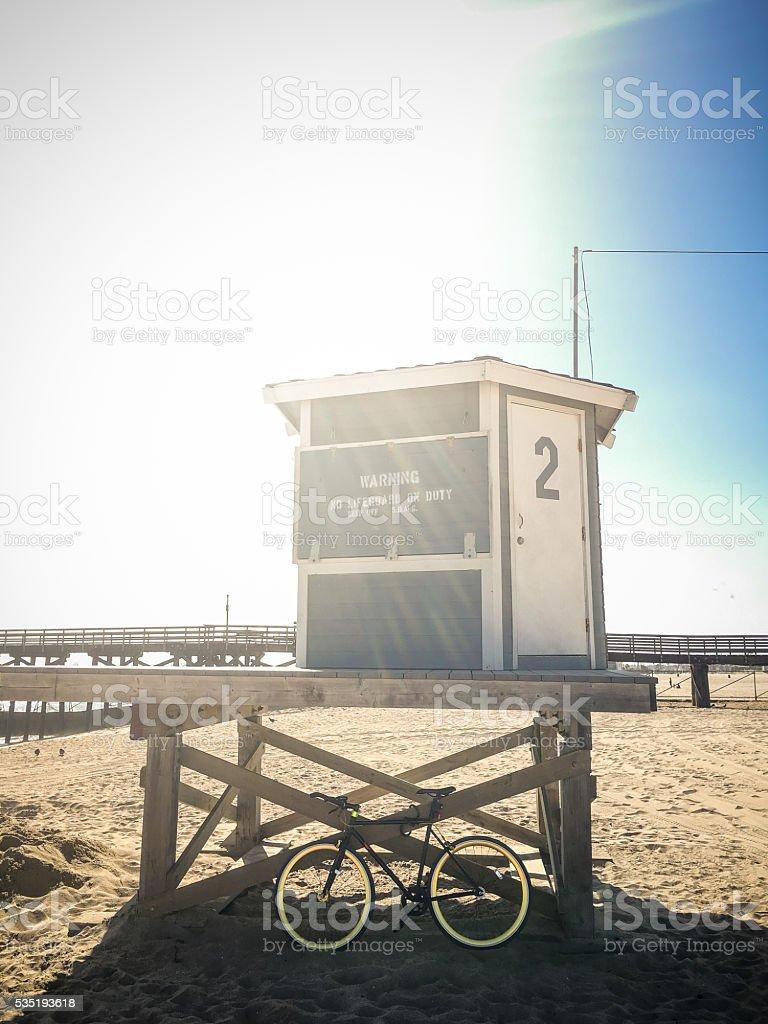 Bike leaning against lifeguard hut on beach stock photo
