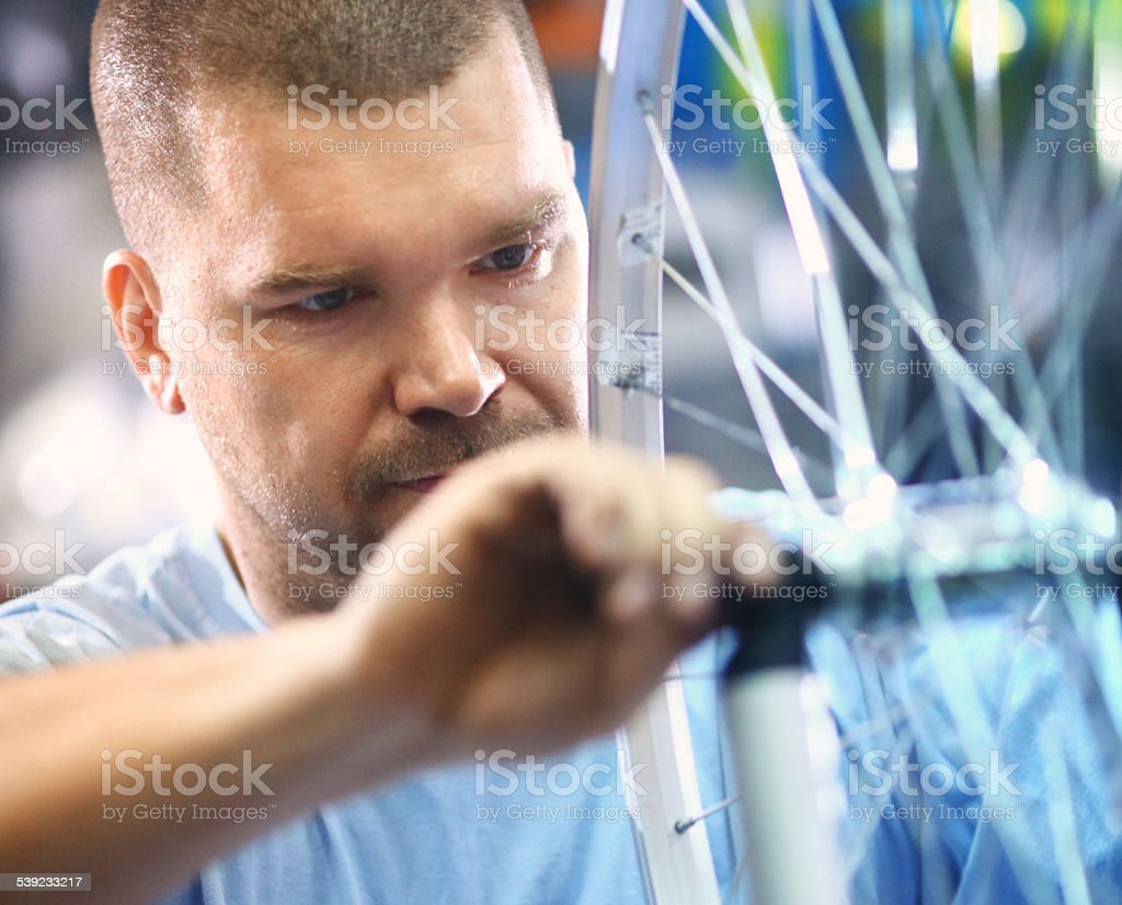 Bike mechanic repairing a wheel. royalty-free stock photo